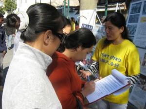 גם עובדים זרים ממדינות אחרות וישראלים מביטים בפוסטרים  ואחר כך חותמים על עצומה להפסקת הרדיפה נגד הפאלון גונג בסין