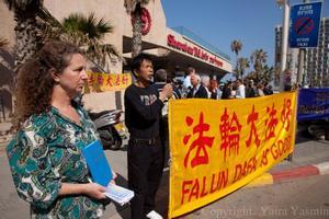 """מתרגלים סינים החיים בישראל הגיעו לתמוך. הם מחזיקים שלט בסינית ובאנגלית. לידם מתרגלת ישראלית מחזיקה את הספר """"ג'ואן פאלון"""" בשפה הרוסית"""