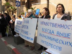 ישראלים עם שלטים ברוסית ועם הספר שהוחרם ברוסיה עקב השפעת המשטר הקומוניסטי בסין