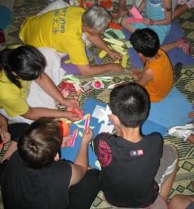 ילדים והוריהם מכינים פרחי לוטוס מנייר צבעוני  ושומעים על הפאלון דאפא