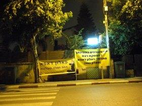 מתרגלי פאלון דאפא עומדים עם שלטים מול ביתה של ציפי לבני